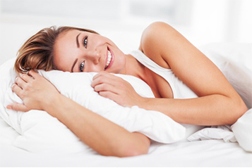 Eine Frau liegt lächeln auf ihrem Kopfkissen