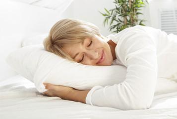 Eine Frau schläft auf einem Wasserkopfkissen und sieht ausgeruht aus.
