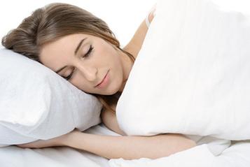 Eine Frau schläft auf in Ihrem Bett auf der Seite